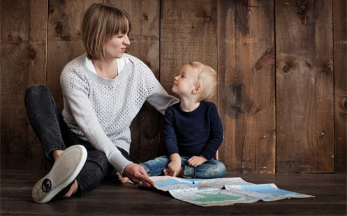 Mother smiling and helping her son read a map